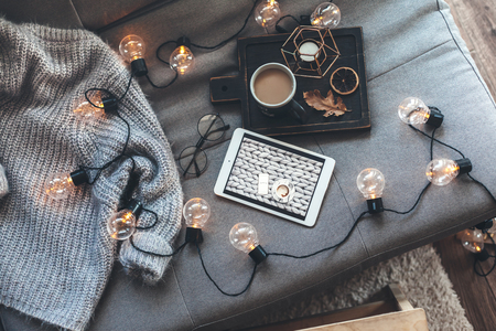 Still life details of living room. Cup of coffee on rustic wooden tray, tablet and warm woolen sweater on sofa, decorated with led lights, top view point. Autumn weekend concept. Watching movie. Stockfoto