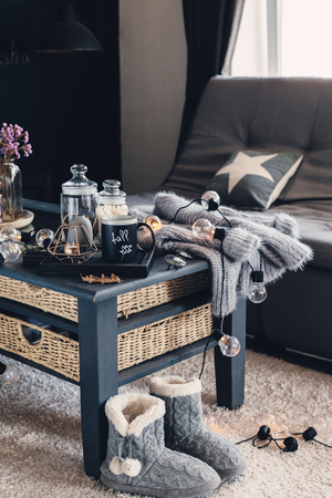 Still life details of living room interior. Cup of coffee on rustic wooden tray, candle and warm woolen sweater on table, decorated with led lights. Autumn weekend concept. Fall home decoration. Imagens