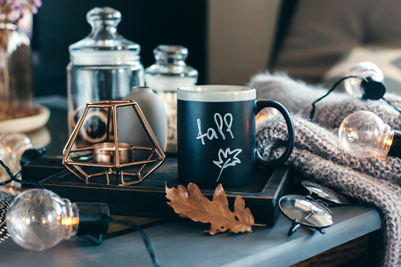 거실의 정물화 세부 정보입니다. 소박한 나무 용지함, 촛불 및 테이블에 따뜻한 모직 스웨터에 커피 한잔 led 조명으로 장식. 가 주말 개념입니다. 가 가정 장식.