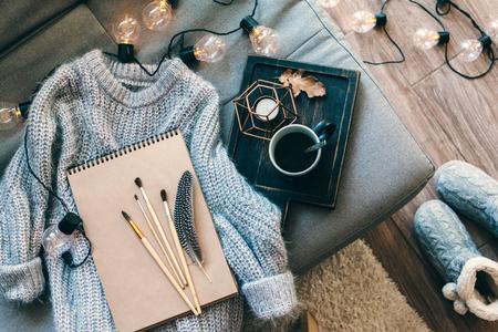 아직도 인생 세부입니다. 소박한 나무 쟁반, 스케치북, 따뜻한 조명 모직 스웨터 소파에 커피 한잔, led 조명, 상위 뷰 포인트 장식. 가 주말 개념입니다. 스톡 콘텐츠