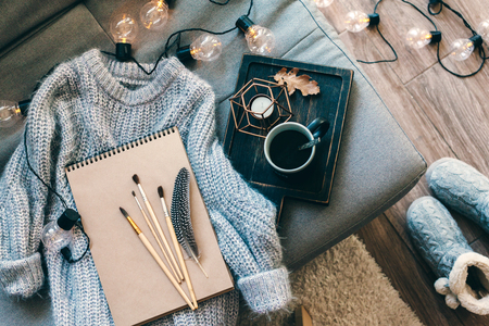 Still life details. Cup of coffee on rustic wooden tray, sketchbook and warm woolen sweater on sofa, decorated with led lights, top view point. Autumn weekend concept. Hobby and crafts. Stockfoto