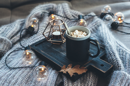 Still life details of living room. Cup of coffee on rustic wooden tray, candle and warm woolen sweater on sofa, decorated with led lights. Autumn weekend concept. Fall home decoration. Archivio Fotografico