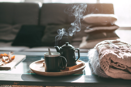 Still life details in home interior of living room. Sweaters and cup of tea with steam on a serving tray on a coffee table. Breakfast over sofa in morning sunlight. Cozy autumn or winter concept. Stok Fotoğraf