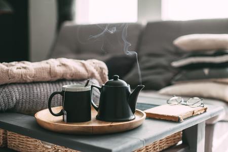 Dettagli di natura morta all'interno della casa del salotto. Maglioni e tazza di tè con vapore su un vassoio da portata su un tavolino da caffè. Colazione sul divano nella luce del sole del mattino. Accogliente concetto di autunno o inverno. Archivio Fotografico