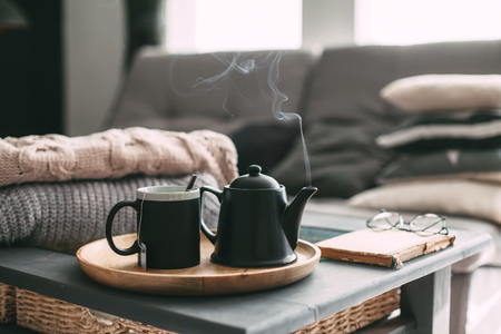 Still life details in home interior of living room. Sweaters and cup of tea with steam on a serving tray on a coffee table. Breakfast over sofa in morning sunlight. Cozy autumn or winter concept. Stock Photo