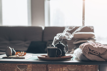 Still life details in home interior of living room. Sweaters and cup of tea with steam on a serving tray on a coffee table. Breakfast over sofa in morning sunlight. Cozy autumn or winter concept. 写真素材