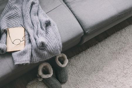 Kasjmier trui en lezen op grijze bank. Warm weekend thuis. Detail van gezellig winter interieur. Stockfoto