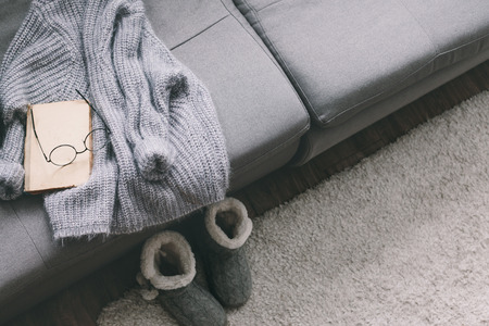 Cashmere sweater and reading on gray sofa. Warm weekend at home. Detail of cozy winter interior. Archivio Fotografico