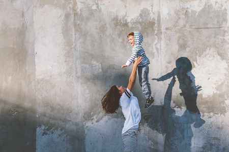 Young beautiful mom with her son wearing casual clothes: striped hoodie, t-shirt and and pants posing against city wall, minimalist street fashion style, same look, family outfit for parent and child.
