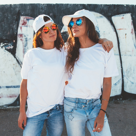 Two models wearing plain white t-shirts and hipster sunglasses posing against street wall. Teen urban clothing style, same look. Mockup for tshirt print store. Foto de archivo