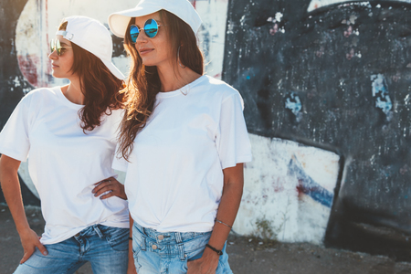 Two models wearing plain white t-shirts and hipster sunglasses posing against street wall. Teen urban clothing style, same look. Mockup for tshirt print store. Stock Photo