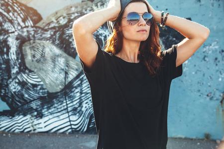 모델 착용 일반 검은 색 t- 셔츠와 hipster 선글라스 스트리트 벽, 십 대 도시 의류 스타일, mockup tshirt 인쇄 저장소에 대 한 포즈