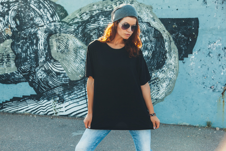 Model wearing plain black t-shirt and hipster sunglasses posing against street wall, teen urban clothing style, mockup for tshirt print store