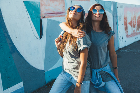 Two models wearing plain gray t-shirts and hipster sunglasses posing against street wall. Teen urban clothing style, same look. Mockup for tshirt print store.