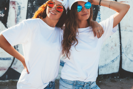 Two models wearing plain white t-shirts and hipster sunglasses posing against street wall. Teen urban clothing style, same look. Mockup for tshirt print store. Banque d'images
