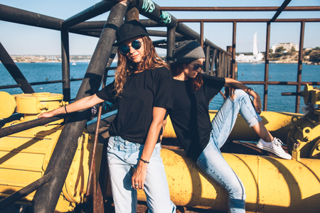 Two model wearing plain black t-shirt and hipster sunglasses, teen urban clothing style, mockup for tshirt print store Foto de archivo
