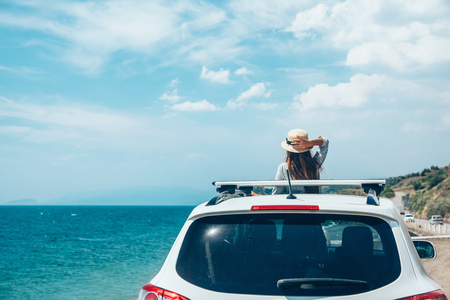 Rear view of pre teen child in car over sea view on summer roadtrip to the beach
