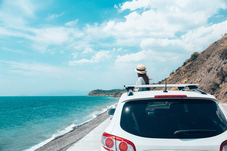Rear view of pre teen child in car over sea view on summer roadtrip to the beach Stock Photo - 87208584
