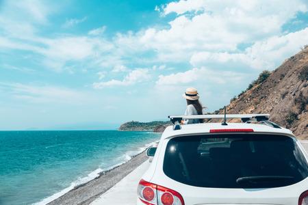 Vista trasera del niño pre adolescente en el coche sobre la vista al mar en el camino de verano a la playa Foto de archivo - 87208584