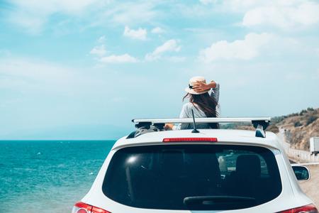 Vista posteriore del bambino pre teen in automobile sopra la vista del mare sulla roadtrip di estate alla spiaggia Archivio Fotografico - 87208586