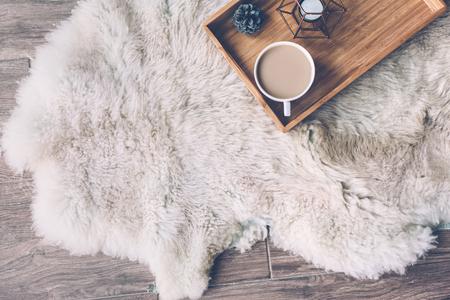 Becher mit Kaffee und Wohnkultur auf hölzernem Umhüllungsbehälter auf Schafhautwolldecke. Winterwochenendenkonzept, Draufsicht Standard-Bild