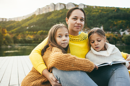 Family spending time together by the lake in autumn. Mom with her daughters reading book near the pond. Fall weekend in the open air.