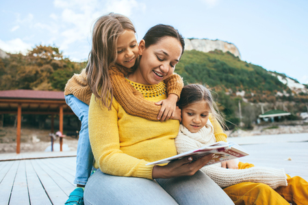 Family spending time together outdoors in autumn. Mom with her daughters reading book in park. Fall weekend in the open air. Stock Photo