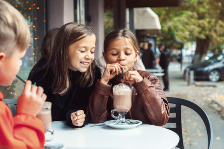 Children having fun in outdoor cafe. Kids talking and drinking cocoa for the breakfast in the city street in autumn. Spending weekend with friends. Zdjęcie Seryjne - 88061748