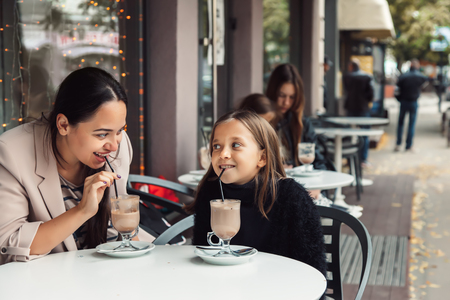 Mom with child spending time in outdoor cafe. Mother with her daughter talking and drinking cocoa for the breakfast in the city street in autumn. Urban family weekend. Stock fotó - 88143332