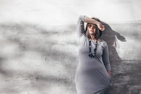 ミニマリストグレーのマキシドレス、サングラス、ストリートウォールの上にポーズをとるジュエリーを身に着けたボブヘアカットとプラスサイズ