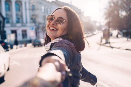 Young stylish woman wearing leather jacket and sunglasses walking on the city street in spring. Casual look, elegant style. Plus size fashion outfit.