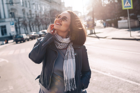 Young stylish woman wearing gray maxi dress and leather jacket walking on the city street in spring. Casual look, elegant style. Plus size fashion outfit.