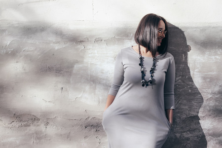 Plus size model with bob haircut wearing minimalist gray maxi dress, sunglasses and jewelry posing over street wall.