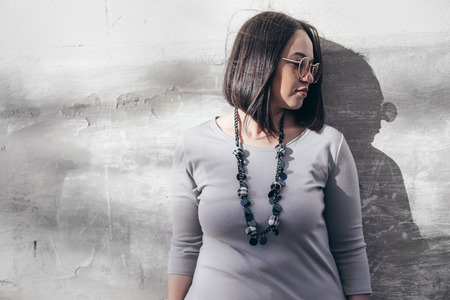 Plus size model with bob haircut wearing minimalist gray maxi dress, sunglasses and jewelry posing over street wall.