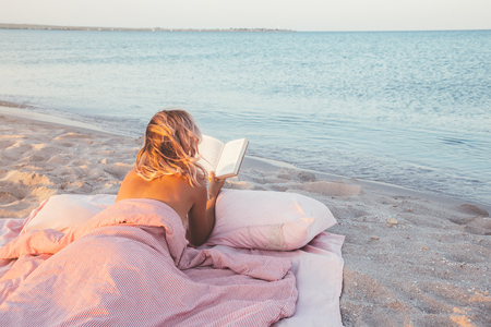 Woman reading a book on cozy and comfortable bed near the sea.