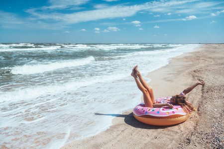 Girl relaxing on donut lilo on the beach. Playing with inflatable ring. Summer holiday idyllic on a tropical island. 免版税图像