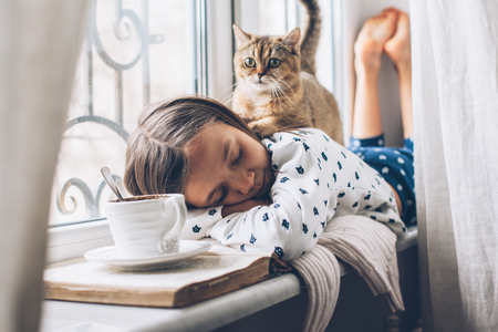 Child in pajamas relaxing on a window sill with pet. Lazy weekend with cat at home. Cozy scene, hygge concept. Reklamní fotografie - 97958397