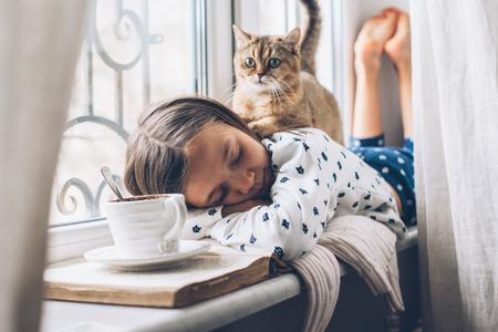 Niño en pijama relajante en el alféizar de una ventana con mascota. Fin de semana perezoso con gato en casa. Escena acogedora, concepto de higiene. Foto de archivo