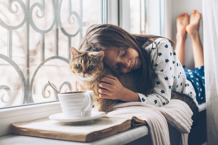 Child in pajamas relaxing on a window sill with pet. Lazy weekend with cat at home. Cozy scene, hygge concept.