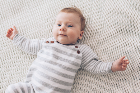 Portrait Of A Cute 2 Month Old Baby Lying Down On A Crochet Blanket