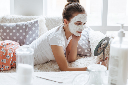 12 years old preteen relaxing on the sofa and making clay facial mask. Teenage girl doing anti blemish skin treatment. Morning skin care routine. Banque d'images