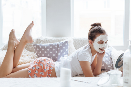 12 years old preteen relaxing on the sofa and making clay facial mask. Teenage girl doing anti blemish skin treatment. Morning skin care routine. Archivio Fotografico