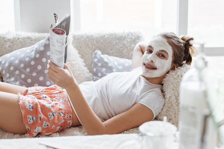 12 years old preteen relaxing on the sofa and making clay facial mask. Teenage girl doing anti blemish skin treatment. Morning skin care routine. Reklamní fotografie