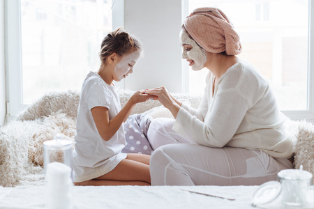 Mom with her daughter making clay face mask. Mother with child doing beauty treatment together. Morning skin care routine.