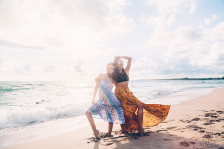 Two boho friends (girls) wearing floral maxi dress and skirt walking on the sea shore. Bohemian clothing style. Standard-Bild - 97958992