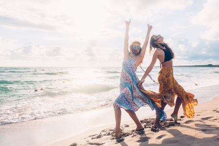 Two boho friends (girls) wearing floral maxi dress and skirt dancing on the sea shore. Bohemian clothing style.
