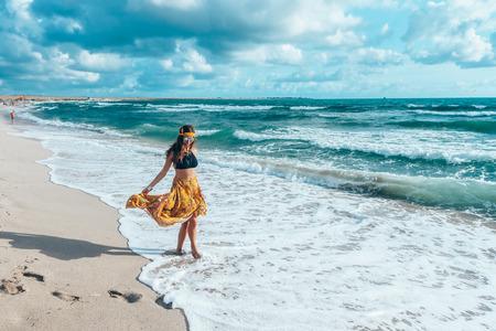 Girl wearing floral maxi skirt walking barefoot on the sea shore. Bohemian clothing style. Standard-Bild