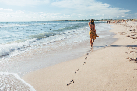 Girl wearing floral maxi skirt walking barefoot on the sea shore. Bohemian clothing style. Stockfoto