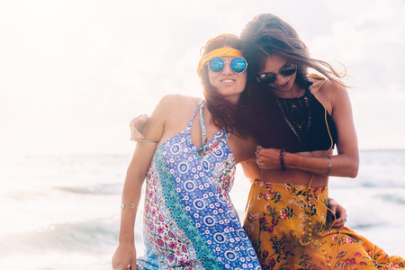 Two boho friends (girls) wearing floral maxi dress and skirt walking on the sea shore. Bohemian clothing style. Standard-Bild - 98036145