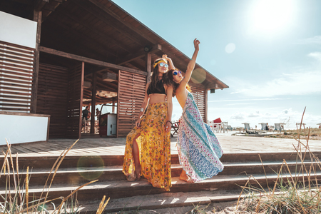 Two boho friends (girls) wearing floral maxi dress and skirt relaxing on the beach. Bohemian clothing style. Stock fotó